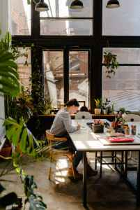 photo of woman sitting by the table